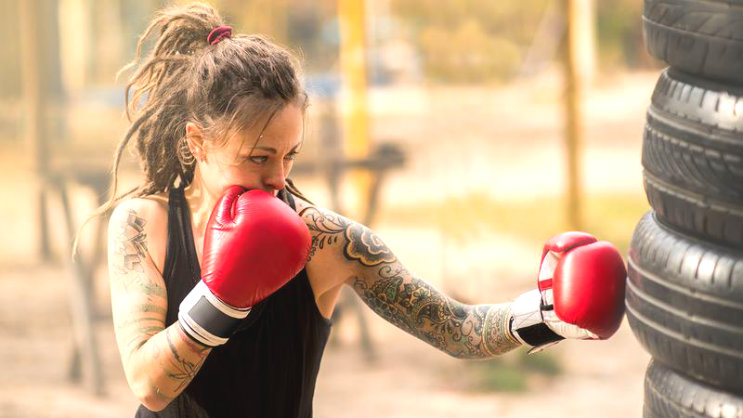 beautiful young woman with tattoos doing boxing practice