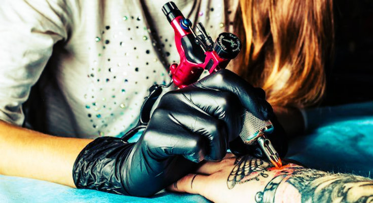 a woman tattoo artist making a tattoo on a person's hand