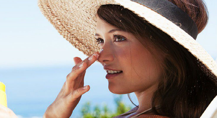 beautiful woman wearing cane hat and applying sun protection cream