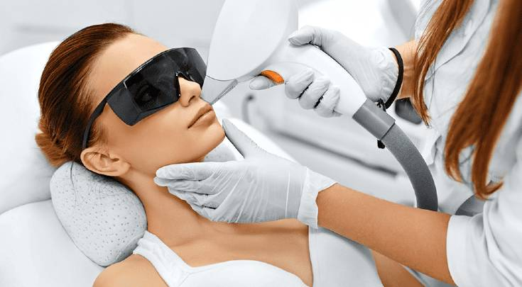 beautiful woman getting laser treatment on face