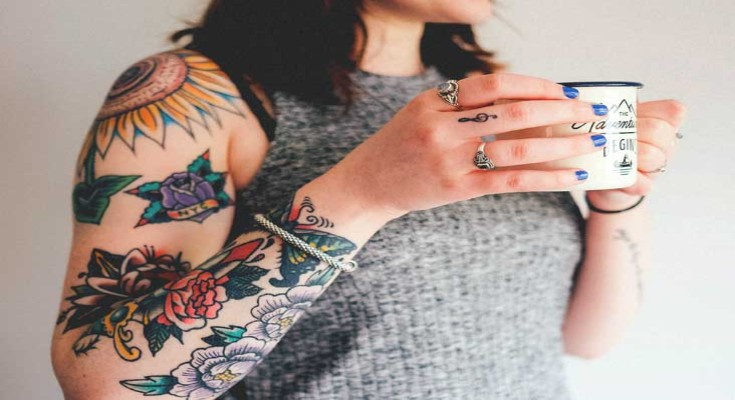 A beautiful girl with tattoo on arm is holding a mug