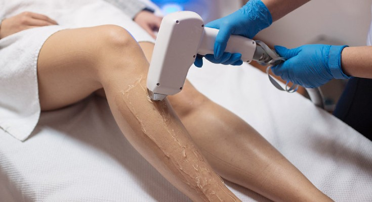 a young woman is having gel on legs
